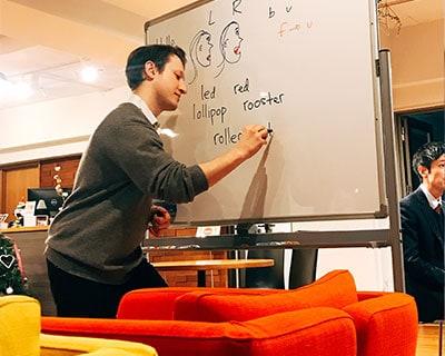 先生はホワイトボードに発音の仕方を書いて違いを説明しています
