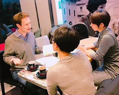 先生と女性の生徒2人がカフェでリラックスしながら英語を勉強しています