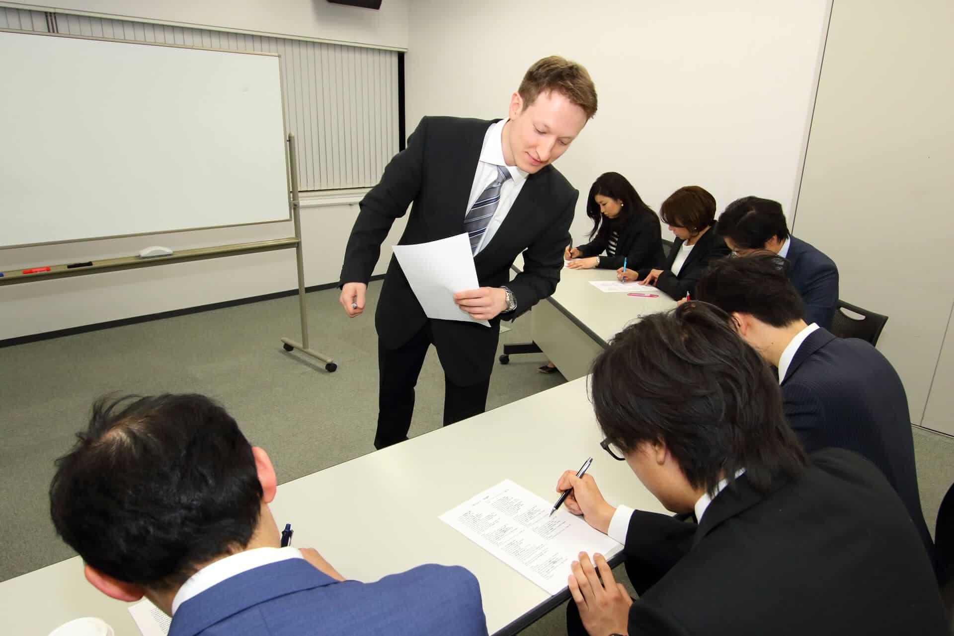 先生はビジネス英会話のクラスで生徒が書いている様子をチェックし、進捗をみています