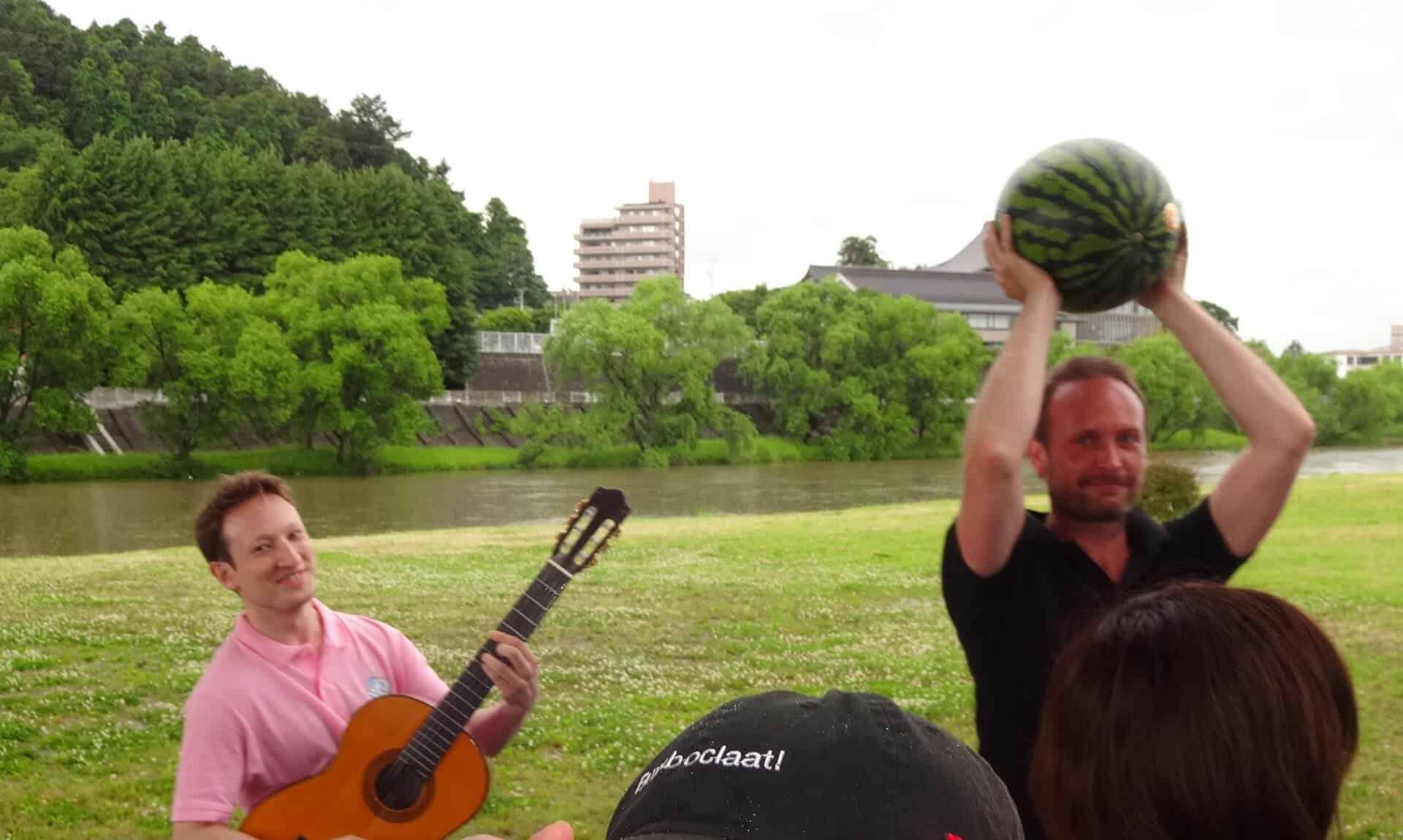 ピンクの服を着た先生がギターを弾き、黒の服を着た先生がスイカを頭の上で持っています