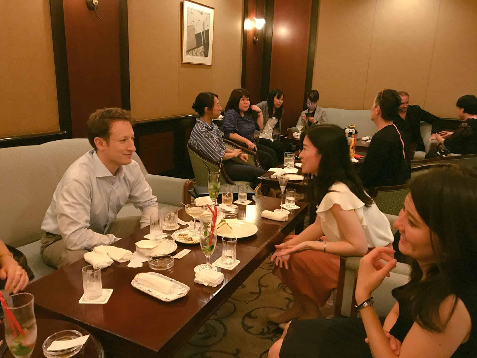 カクテルナイトのイベントで先生と生徒がお酒を飲みながら楽しくお話をしています