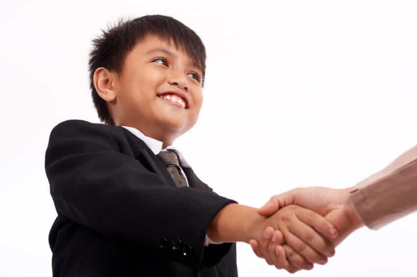 男の子が誰かと握手をしながらはにかんでいます