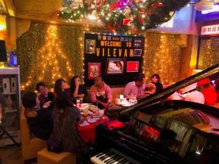 クリスマスパーティージャズ-ビレバンピアノと坐っている生徒