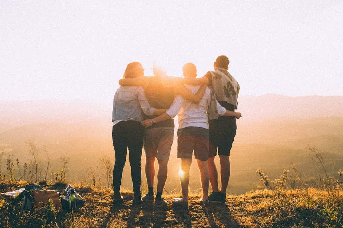 友達4人で山の上から朝日を見ています