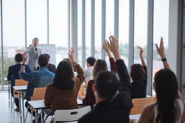 生徒たちはクラスルームで手を上げている