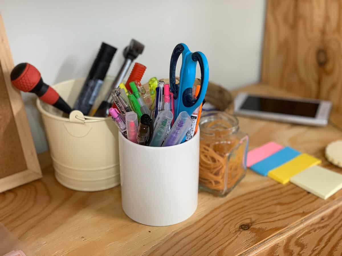 木の机の上にたくさんの文房具と携帯電話が置いてあります