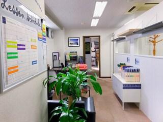 長い廊下、大きな植物とソファのある大きなロビーの眺め、右側に教室、左側に受付