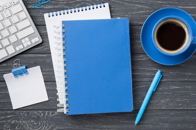 パソコンとノートとコーヒーがテーブルの上に