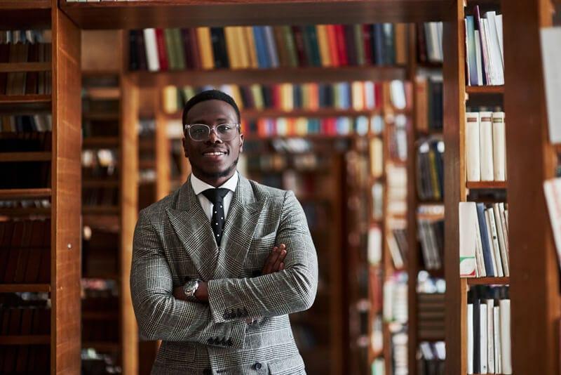 黒人男性が図書館で腕組みをしている