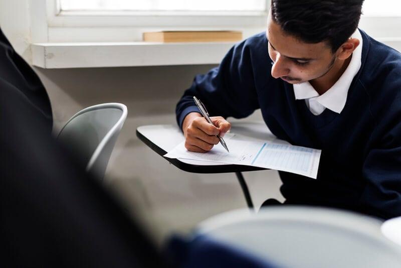 男子学生が授業を聞きながら何かを書いている