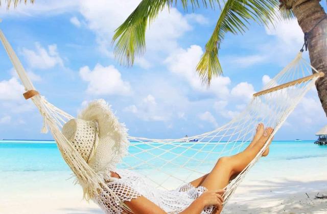 女の人が青い海の砂浜とヤシの木の下でリラックスしています